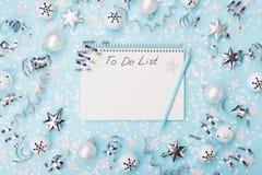 与要做名单的笔记本装饰用五彩纸屑、星和球在蓝色背景顶视图 圣诞节和新年计划 免版税库存图片