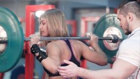 与观看她的教练员的妇女举的杠铃在健身房 库存图片