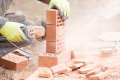 与角度研磨机工具的砖切口 库存照片