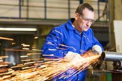与角度研磨机的钢建筑工人研的金属 免版税图库摄影