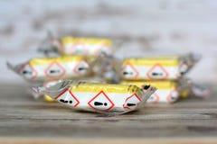 与警告标记的黄色被密封的洗涤剂或洗碗机清洁选项在包裹 免版税库存图片