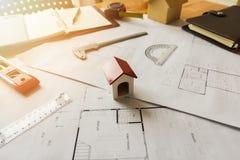 与计划和图纸的一个建筑师房子模型 免版税库存图片