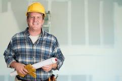 与计划的承包商和在干式墙前面的安全帽 免版税库存照片