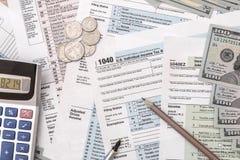 1040与计算器、笔、玻璃和美元的报税表 库存图片