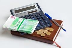 与计算器和笔记薄的金钱 免版税库存照片