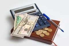 与计算器和笔记薄的金钱 库存图片