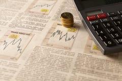 与计算器和金钱的报纸股市 免版税库存图片