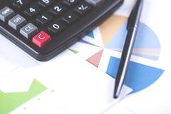 与计算器的在桌上的笔和图表 免版税库存照片