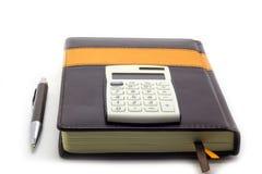 与计算器的在白色背景,业务经理集合的日志和笔 免版税图库摄影