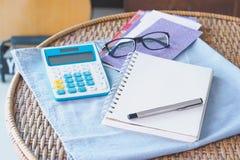 与计算器玻璃笔和书的票据费用在镭顶部 免版税库存图片