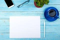 与计算机、笔和一杯咖啡的蓝色办公桌桌,全部事 与拷贝空间的顶视图 库存照片
