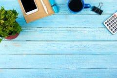 与计算机、笔和一杯咖啡的蓝色办公桌桌,全部事 与拷贝空间的顶视图 免版税库存图片