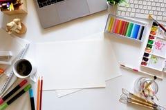 与计算机、设计师供应和咖啡杯的办公室黑暗的白色书桌桌 顶视图工作区和拷贝空间 免版税库存照片