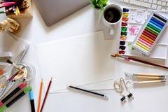 与计算机、设计师供应和咖啡杯的办公室黑暗的白色书桌桌 顶视图工作区和拷贝空间 库存图片