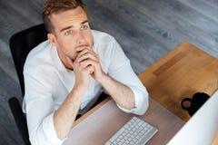 与计算机一起使用和认为在工作场所的沉思商人 免版税库存图片