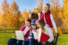 与计算机和咖啡的孩子在公园 免版税库存照片