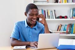 与计算机和cellphon的英俊的非裔美国人的商人 库存图片