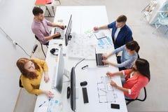 与计算机的创造性的队,图纸在办公室 免版税库存图片