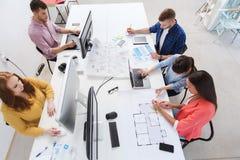 与计算机的创造性的队,图纸在办公室 库存照片
