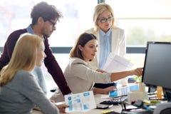 与计算机的愉快的企业队在办公室 免版税图库摄影