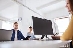 与计算机的愉快的创造性的队在办公室 图库摄影