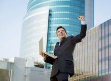 与计算机膝上型计算机愉快的做的胜利标志的成功的商人 库存照片
