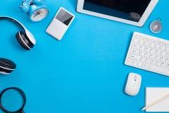 与计算机,无线耳机,警报克洛的蓝色办公桌桌 免版税库存照片