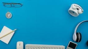 与计算机,无线耳机,警报克洛的蓝色办公桌桌 免版税库存图片
