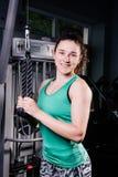 与训练机器的年轻性感的健身妇女锻炼在健身房 库存照片