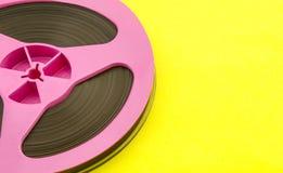 与记录磁带的葡萄酒桃红色音频卷轴在黄色纸背景 时髦流行艺术样式 库存图片