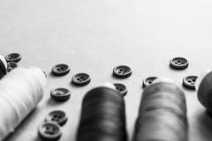 与许多圆的按钮的美好的黑白纹理缝合,毛线针线和卷的  复制空间 平的位置 的treadled 库存图片