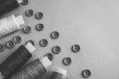 与许多圆的按钮的美好的黑白纹理缝合,毛线针线和卷的  复制空间 平的位置 免版税库存图片