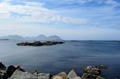 与许多小岩质岛和山背景的庄严海洋风景 免版税库存照片