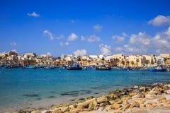 与许多小船的Marsaxlokk历史的口岸在透明海和海滩与石头,马耳他 蓝天和村庄背景 库存图片