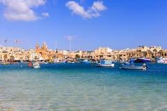 与许多小船的Marsaxlokk历史的口岸在透明海,马耳他 蓝天和村庄背景 免版税库存图片