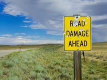 与许多弹孔的公路损伤标志当心在怀俄明 免版税库存照片