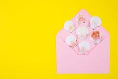 与许多扇贝壳的桃红色信封在色的黄色backgro 免版税图库摄影
