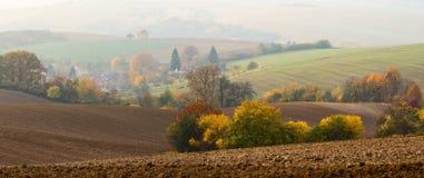 与许多有趣的细节的中间欧洲秋天早晨风景:在阴霾的磨房,吃草鹿牧群,犁了布朗领域 图库摄影