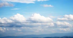 与许多漂移的云彩的明亮的蓝天 库存图片