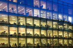 与许多的办公大楼被打开的窗口和已故的办公室工作者里面 伦敦市在黄昏的企业唱腔 免版税库存照片