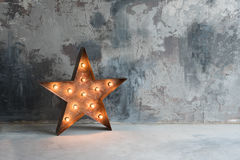 与许多的大装饰减速火箭的星在难看的东西混凝土背景的灼烧的光 美丽的装饰,现代设计 免版税库存照片