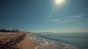与许多的沙滩海草和一些旅馆大厦在距离 有一些溅泼的波浪的安静的海 蓝天 股票录像