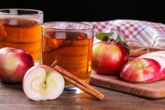 与许多的苹果汁新鲜的红色苹果和桂香在一张棕色木桌上在黑背景 免版税库存照片