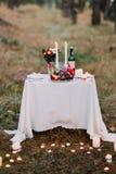 与许多的逗人喜爱的桌浪漫晚餐的燃烧的蜡烛在秋天森林 免版税库存图片