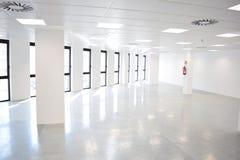 与许多窗口的白色开放空的办公室内部,轻的办公室空间 库存图片