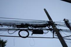 与许多被缠结的缆绳的灯柱,黑缆绳的样式在一根木杆的 库存图片