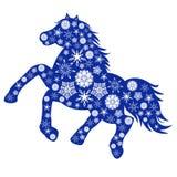 与许多雪花的蓝色马剪影 免版税库存图片