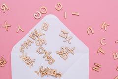 与许多abc信件的被打开的白色信封在桃红色背景 库存照片