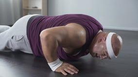 与设法微弱的胳膊的肌肉的懒惰肥胖男性在家做俯卧撑,锻炼 影视素材