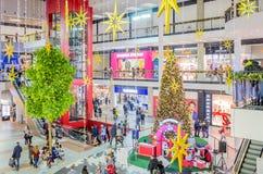 与设计师商店的巨大,多层的购物中心,自动扶梯和顾客在站立的圣诞树的中心 免版税库存图片